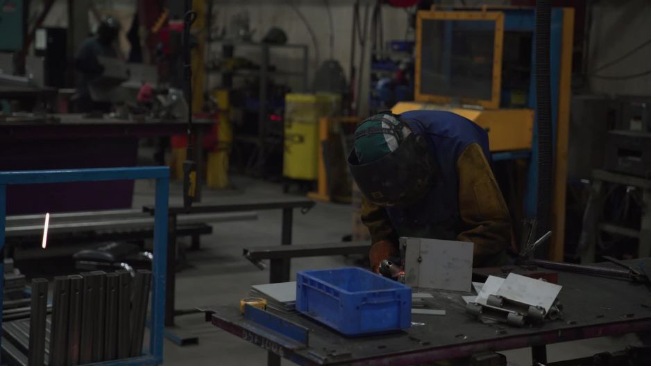 Male industrial worker welding pieces of metal together in ...