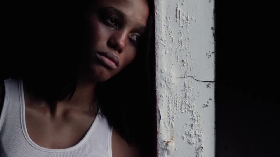 Depressed black woman looking out window in dark room | ClipStock