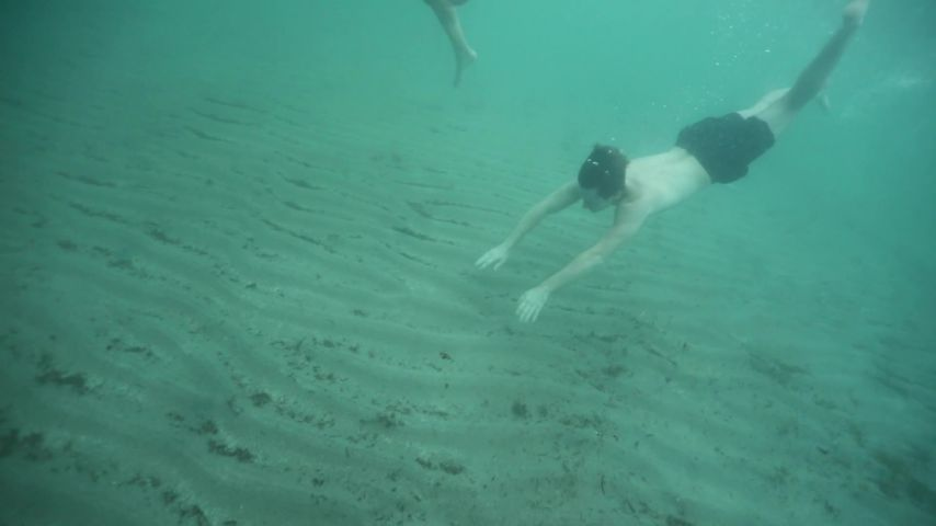 Two Young Women Swimming Underwater Together In The Ocean