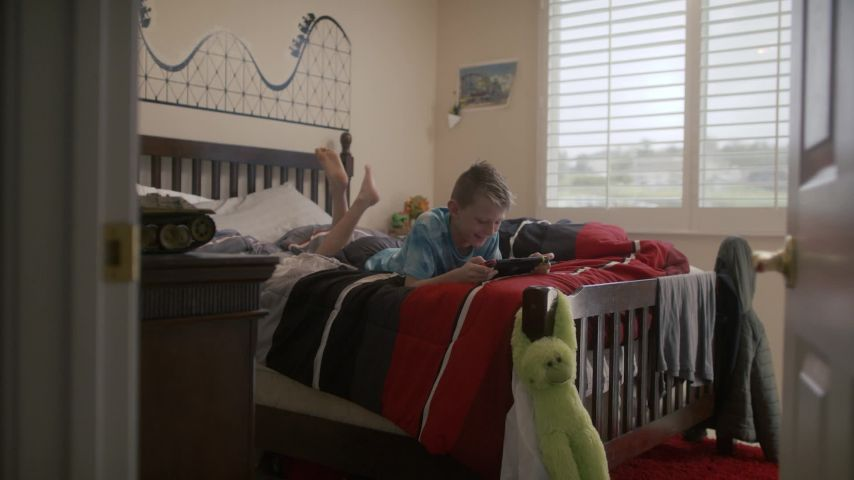 Focused Gamer Boy Playing Nintendo Switch Video Game Console Lying In Bedroom Clipstock